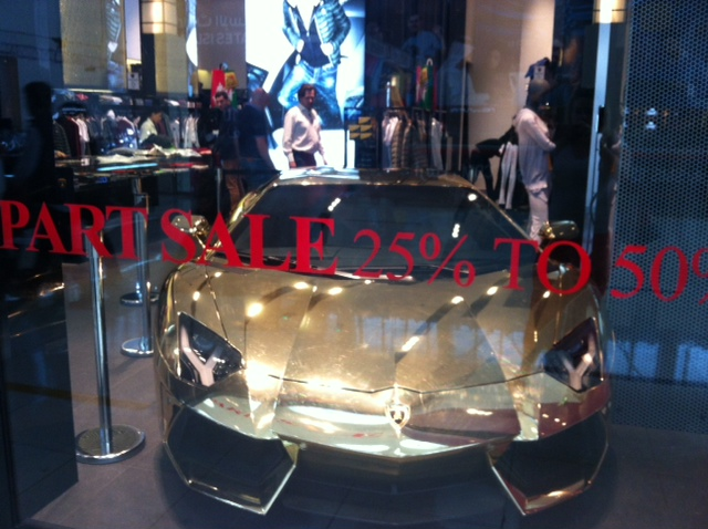 You know the Dubai Shopping Festival has started when … you come across a gold Lamborghini in the window of a clothes shop!